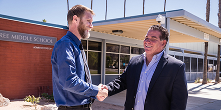 Two men shaking hands in front of school