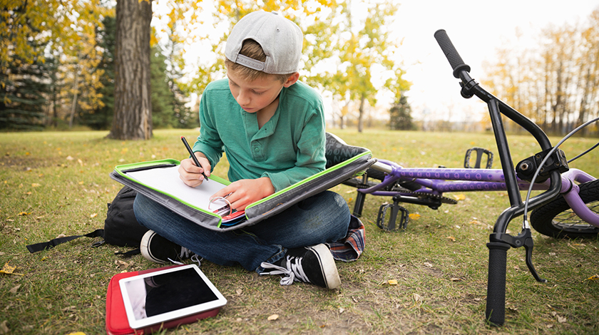 Child writing while sitting in park
