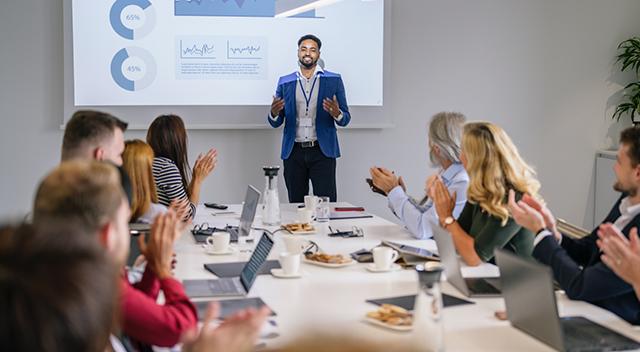 Una sala de conferencias llena de gente aplaudiendo a un hombre con una chaqueta y un cordón dando una presentación con cuadros y gráficos en la pared detrás de él.