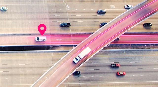 Vista aérea de un gran camión en la carretera con líneas magenta a su alrededor