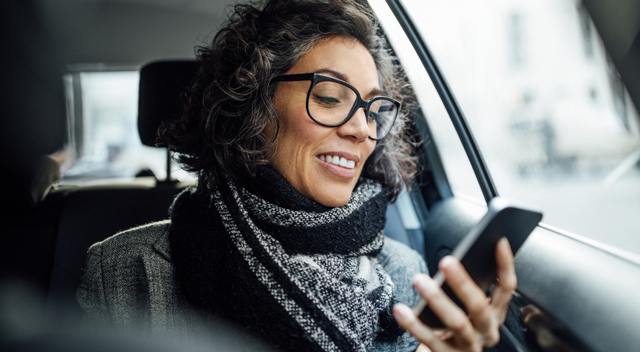 Woman with glasses on her smartphone while riding in a car
