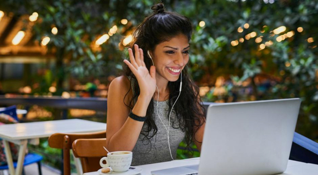 Woman raises a hand while smiling at her laptop in an open seating area