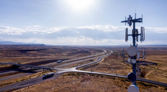 5G tower in the foreground above a highway going into the distance