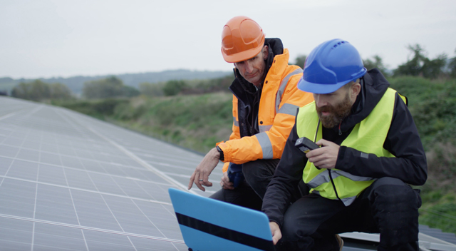 Two technicians work on a laptop in front of solar panels