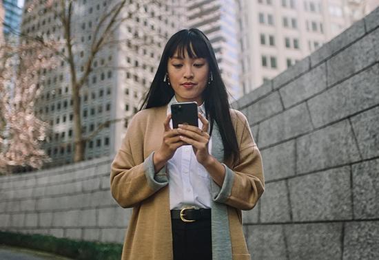 Mujer asiática con un suéter tostado mirando hacia abajo a su smartphoneque sostiene entre sus manos.