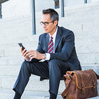 Man in suit sits outside on stairs looking at smartphone