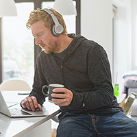 Man wearing headphones looking down at smartphone