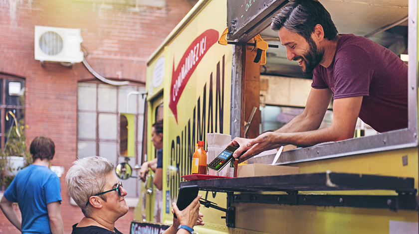 Man in food truck assisting woman customer.