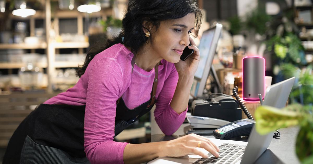Mujer vestida con un suéter rosado usando audífonos telefónicos.