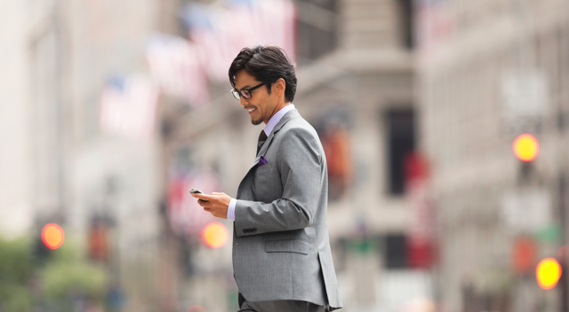 Man on street using smartphone