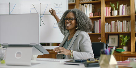 Smiling black woman in a beige suit sits at a table pointing at a white board