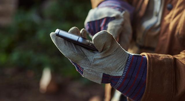 Primer plano de un teléfono CAT en el bolsillo de una chaqueta de campo.
