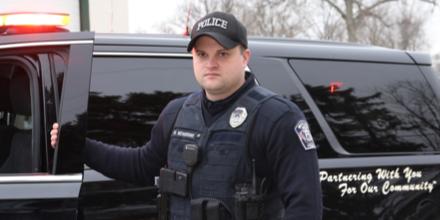 Oficial de policía con una mano en la puerta abierta de su vehículo