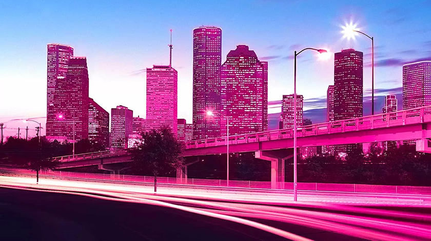 Cluster of city buildings at night with a purple tint.