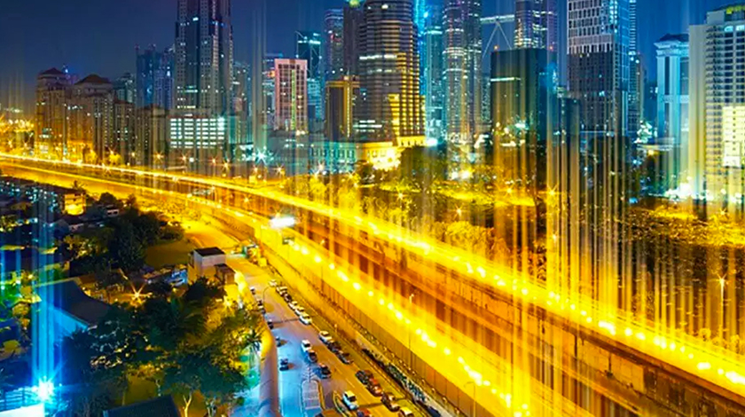 Yellow flash of light depicting motion on a highway surrounding a city at night.