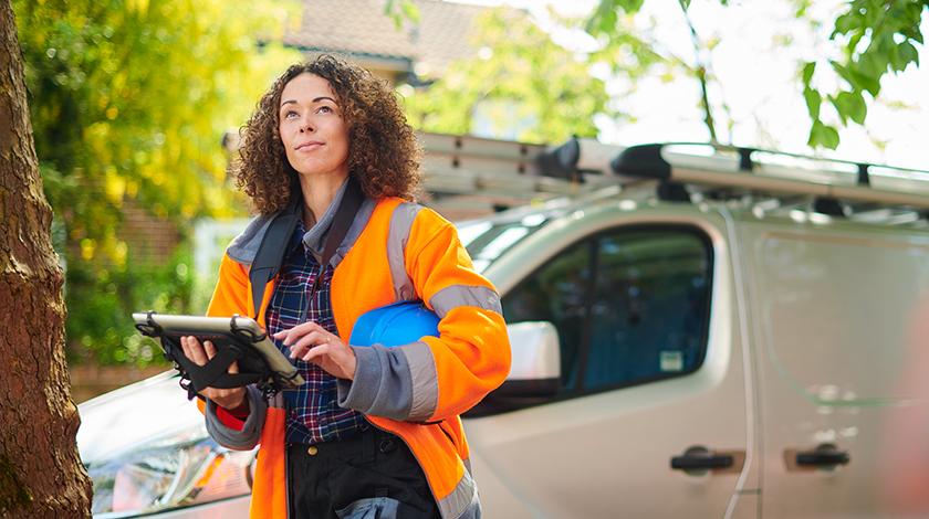 Trabajadora vestida con una chaqueta anaranjada de pie delante de una furgoneta.