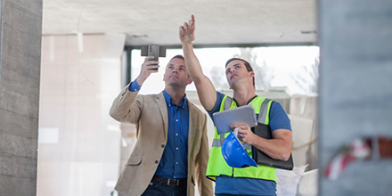 Two men point up to something construction-related and hold a smartphone and tablet.
