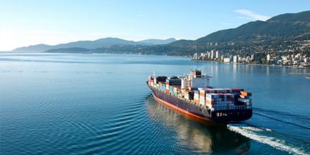 Barco grande con contenedores de carga cerca de la costa de una ciudad con montañas en la distancia