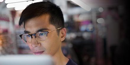 Hombre con gafas mirando la pantalla de su computadora.