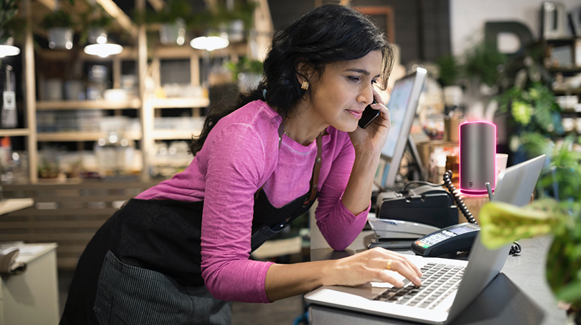 Mujer con camiseta magenta y un delantal negro trabaja en su laptop con el teléfono en el oído