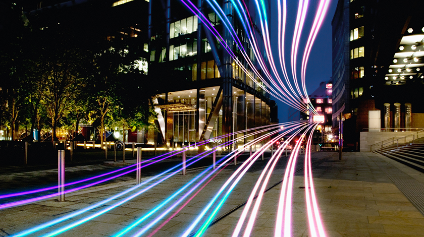 Street in front of an office building with long streaks of blue/purple light moving past.