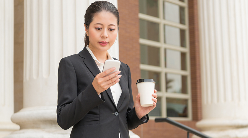Woman in business suit stands while holding a coffee and using her smartphone