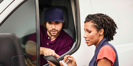 Fleet manager reviewing instructions with a driver in a van