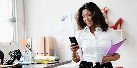 Una mujer en una oficina sosteniendo una carpeta y utilizando un celular.