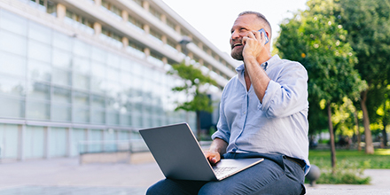 Man sitting outdoors with laptop while talking on smartphone