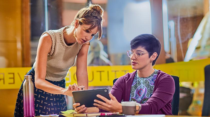 Dos mujeres en un escritorio, una sentada y la otra de pie, mirando una tablet.