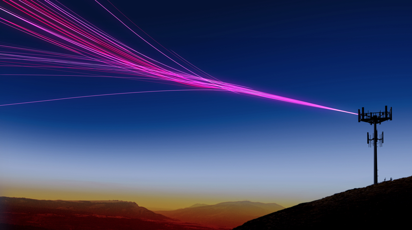 Cell tower on the top of a hill at dusk with magenta beams.