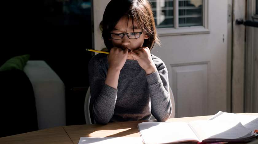 Young student is deep in thought and is doing schoolwork at dining room table.