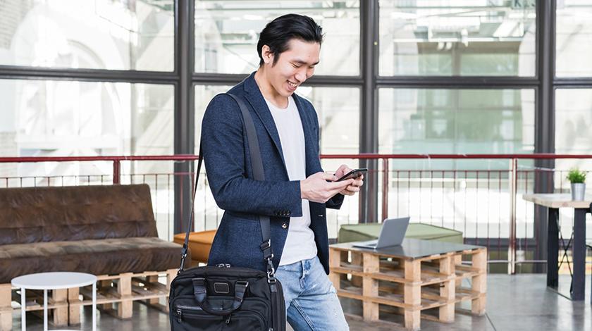 Hombre sonriendo, caminando y usando celular