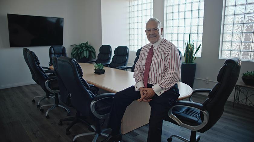 Hombrecon trajey corbata sentado a una mesa de conferencias en una oficina.