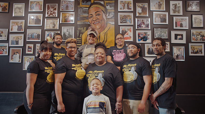 Una familia delante de una pared cubierta con fotografías