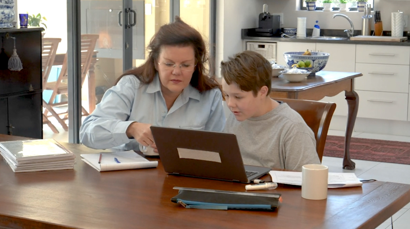 Parental guardian and middle school-aged student sit at dining table and are focused on a laptop.