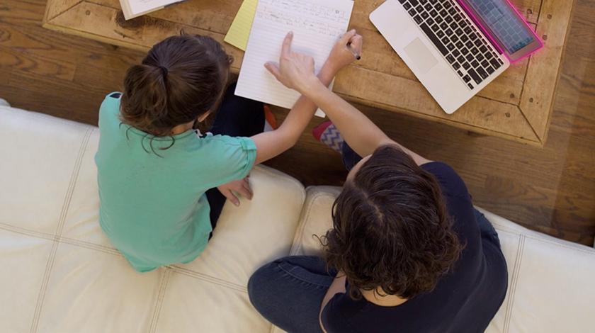 Niño sentado a una mesa en su casa mientras una mujer señala una laptop