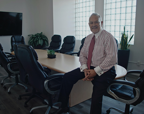 Man in a suit and tie sits on a conference table in an office.