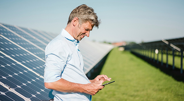 Man outdoors in front of solar panels looking down at his smartphone