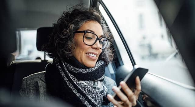 Mujer usando el teléfono dentro de un auto.