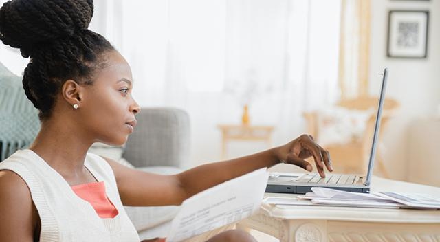 Mujer vestida con un chaleco blanco, luciendo un peinado recogido con una mano sobre una laptop.