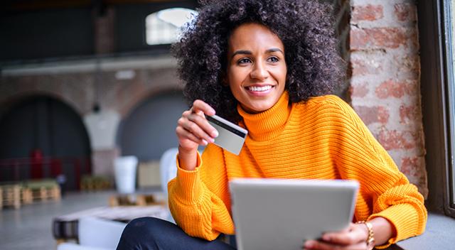 Mujer con cabello rizado vestida con un suéter anaranjado sostiene una tarjeta de crédito y un dispositivo.