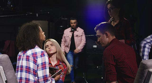 Un equipo de productores alrededor de una mujer en el escenario, hablando mientras ella los escucha.