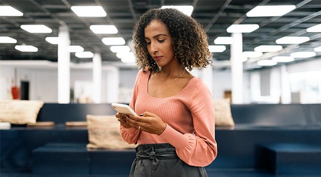 Una mujer con un suéter color durazno utiliza un celular