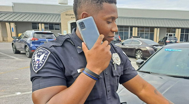 Bay Minette Police Department officer using Samsung smartphone.