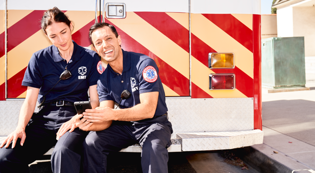 Two EMTs sitting on back of truck