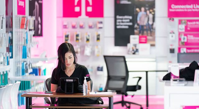 T-Mobile employee wears gloves and interacts with a touchscreen device