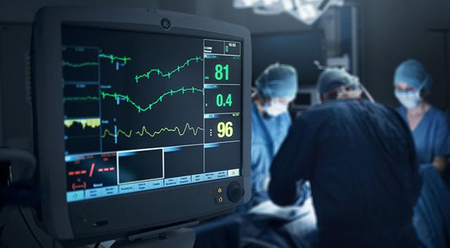 Un quirófano con doctores y un monitor que muestra los signos vitales.