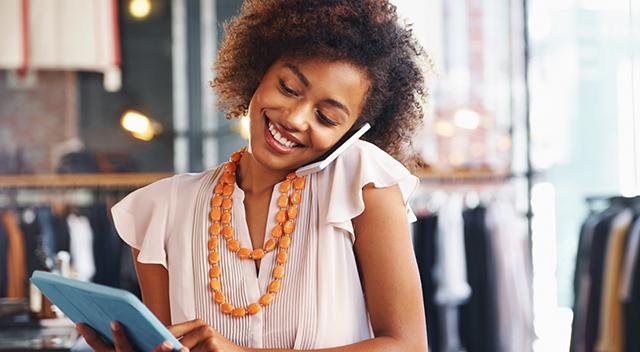 Una mujer en un pequeño negocio habla por teléfono mientras sostiene una tablet.