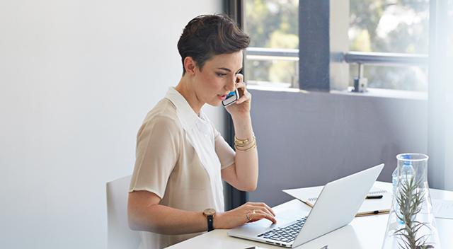 Foto de una mujer sentada a un escritorio con su laptop.